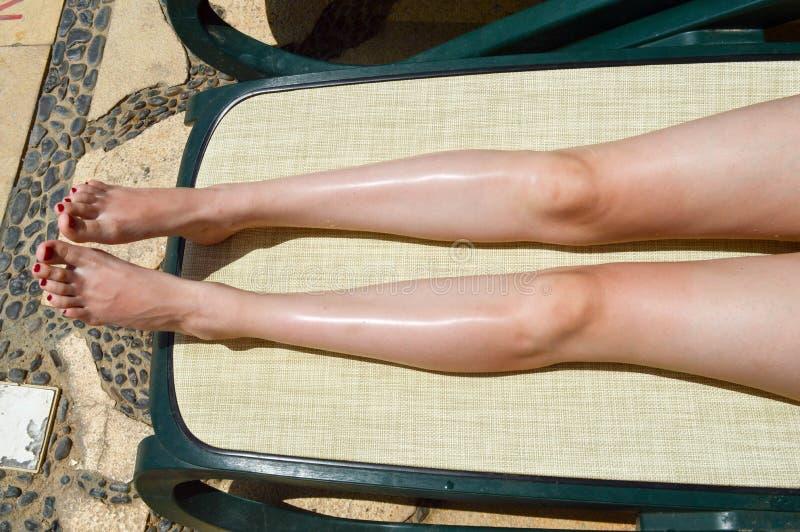 Härliga ben, flickafot, kvinnor med röd manikyr på bakgrunden av en deckchair och pöl på ett tropiskt varmt exotiskt arkivbilder