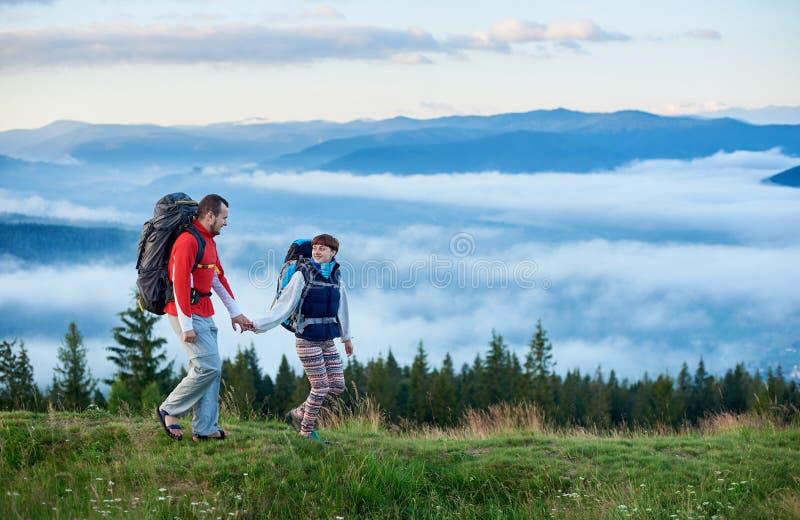 Härliga berg av Carpathians i morgonmist och barnpar som går på grön slinga royaltyfri bild