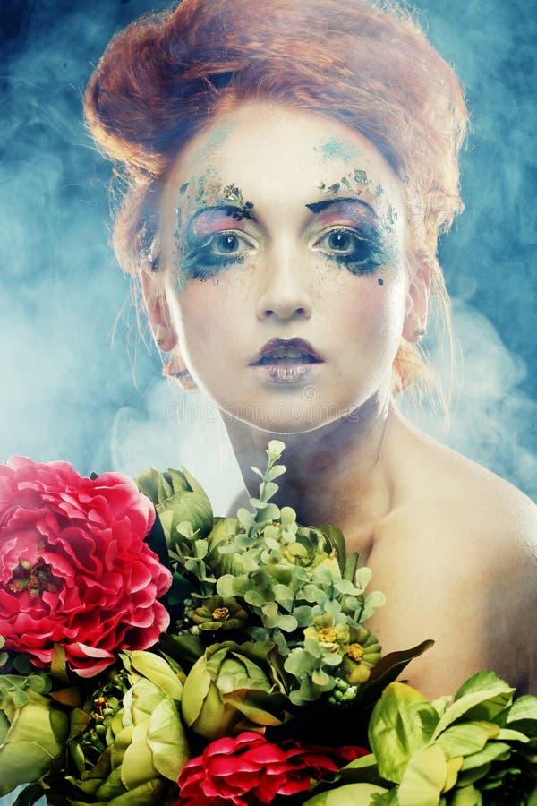 Härliga blommor för redhairkvinnainnehav royaltyfria bilder