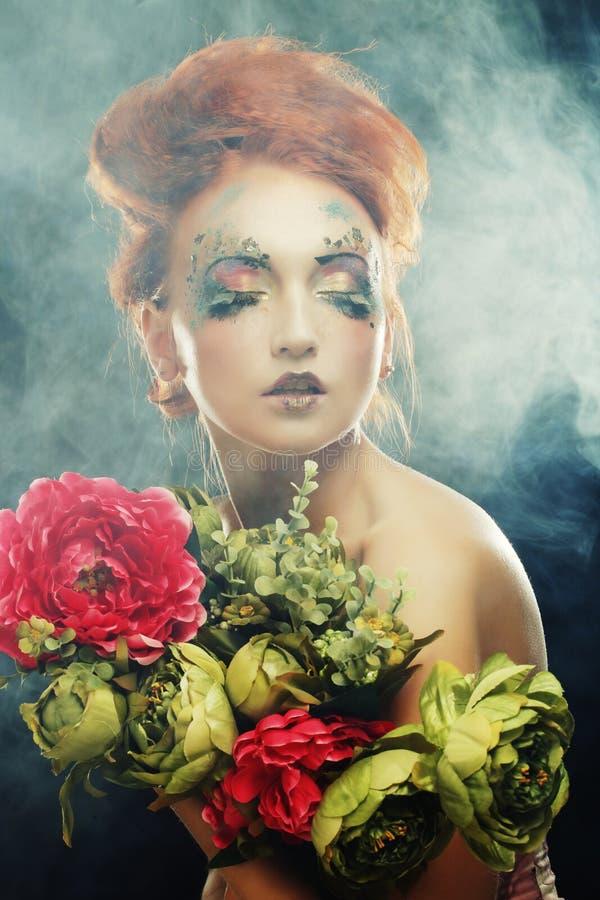 Härliga blommor för redhairkvinnainnehav royaltyfri fotografi