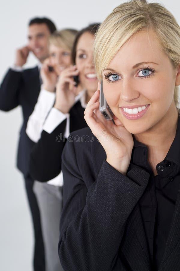 härliga blonda celltelefoner team kvinnan arkivbild