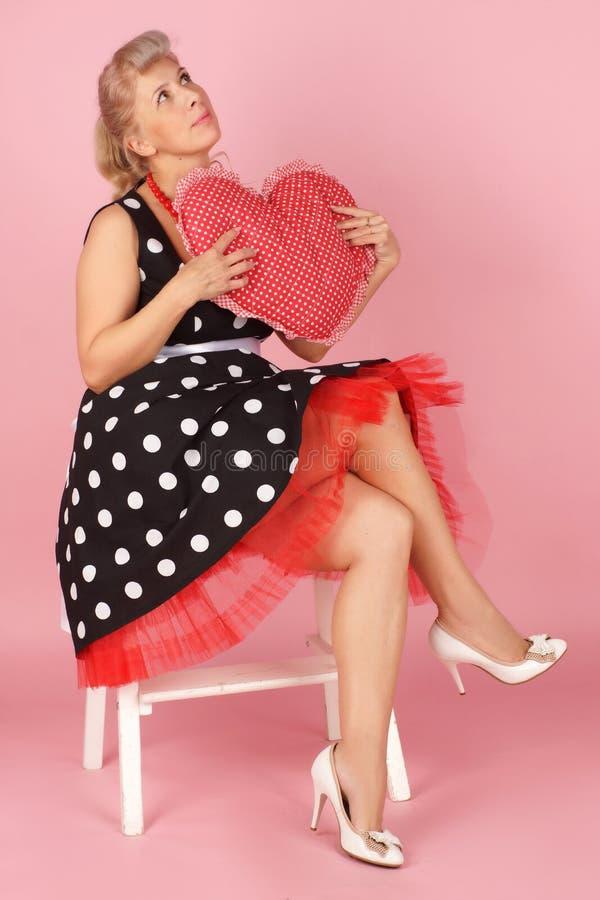 Härliga blonda kvinnadrömmar av förälskelse med enformad kudde i hennes händer, utvikningsbildstil på en rosa bakgrund fotografering för bildbyråer