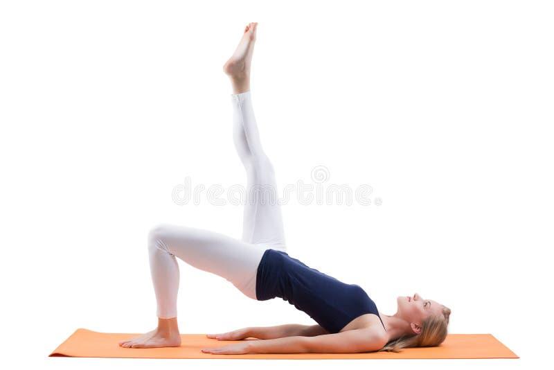 Härliga blonda kvinnautbildningsbakdelar och höftmuskler med raksträcka ett ben på ett mattt royaltyfria foton