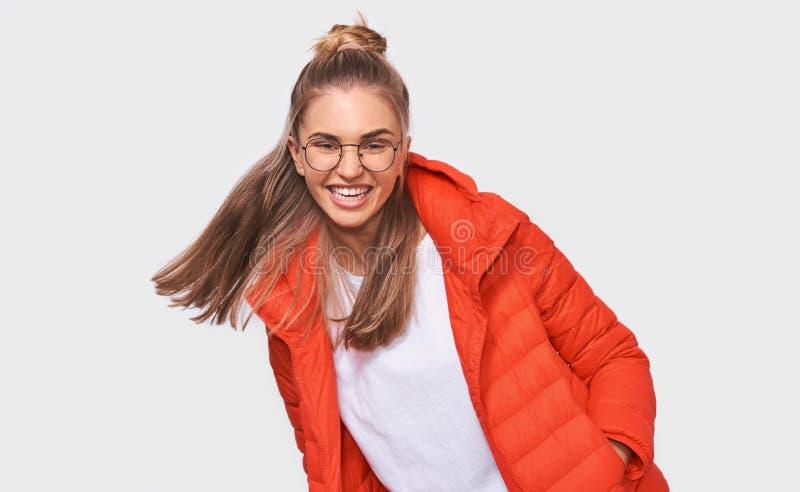 Härliga blonda skratt för ung kvinna på något den roliga iklädda vita t-skjortan och det röda omslaget, bärande rund eyewear arkivbild