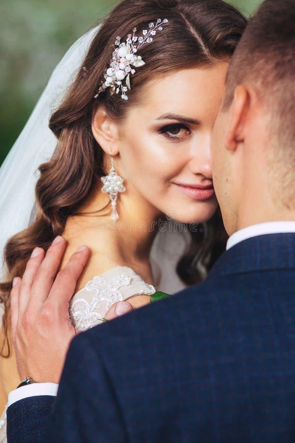 Härliga brölloppar parkerar in De kysser och kramar sig royaltyfri foto