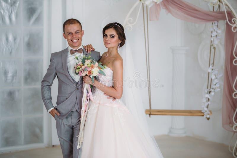 Härliga brölloppar som kramar i ljus studio Brudgummen i en affärsgrå färg passar, en vit skjorta i en fluga och a arkivbild