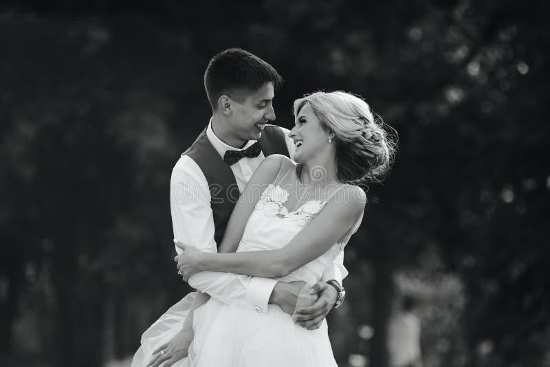 Härliga brölloppar som kramar i parkera royaltyfri fotografi