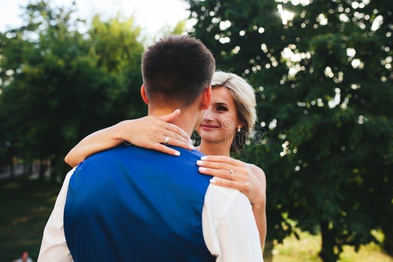 Härliga brölloppar som kramar i parkera royaltyfri foto
