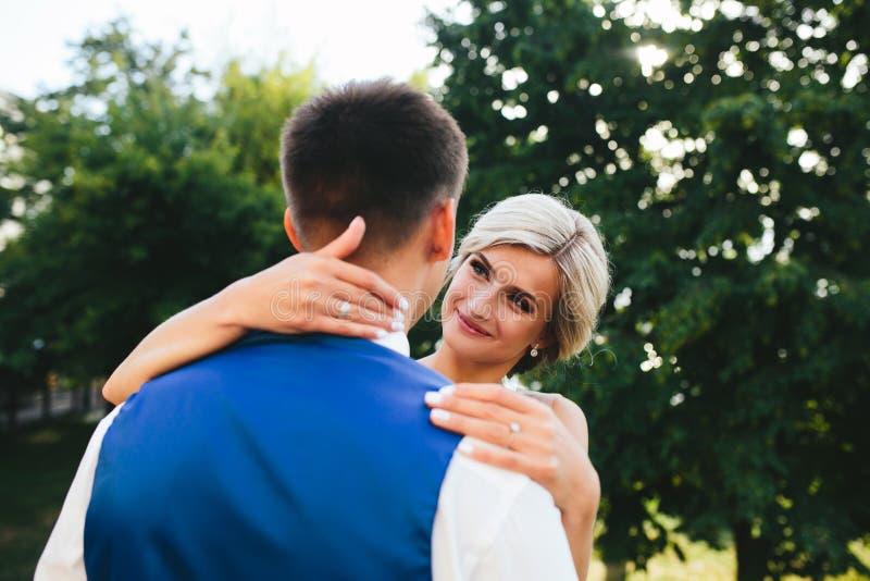 Härliga brölloppar som kramar i parkera arkivbilder
