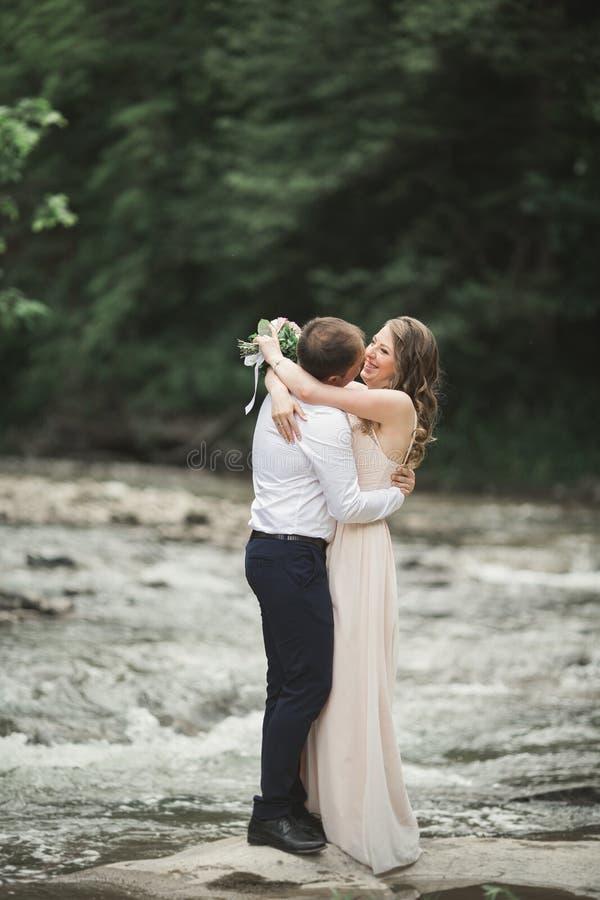 Download Härliga Brölloppar Som Kysser Och Omfamnar Nära Kusten Av En Bergflod Med Stenar Fotografering för Bildbyråer - Bild av majestätiskt, sörja: 78726651