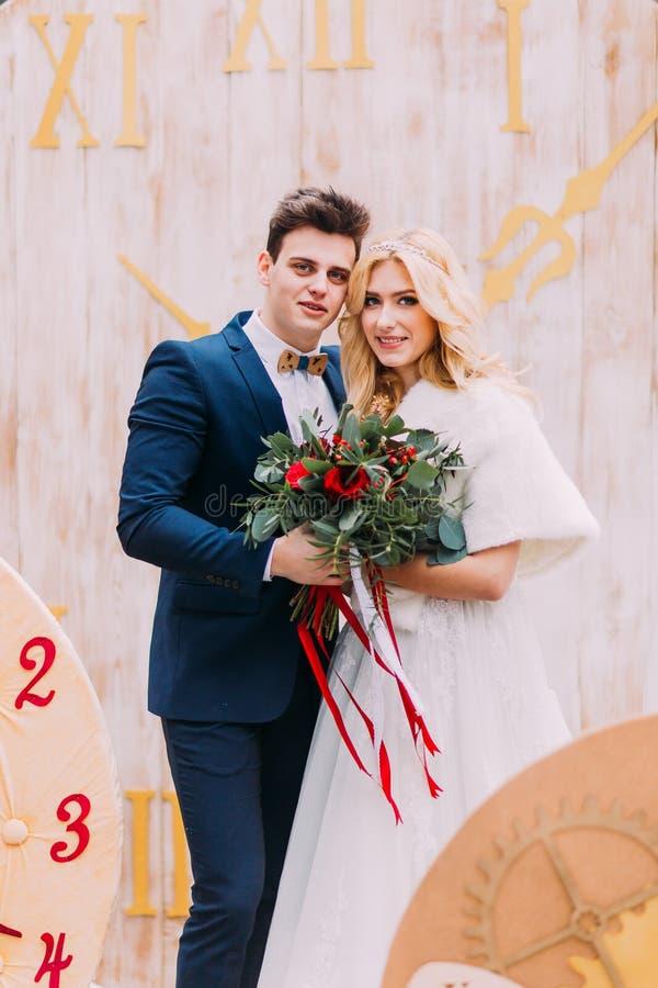 Härliga brölloppar som poserar med buketten av röda rosor Idérika garneringar på bakgrund royaltyfri fotografi
