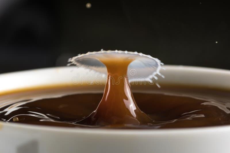 Härliga bristningar av mjölkar droppar på yttersidan av kaffecloseupen fotografering för bildbyråer
