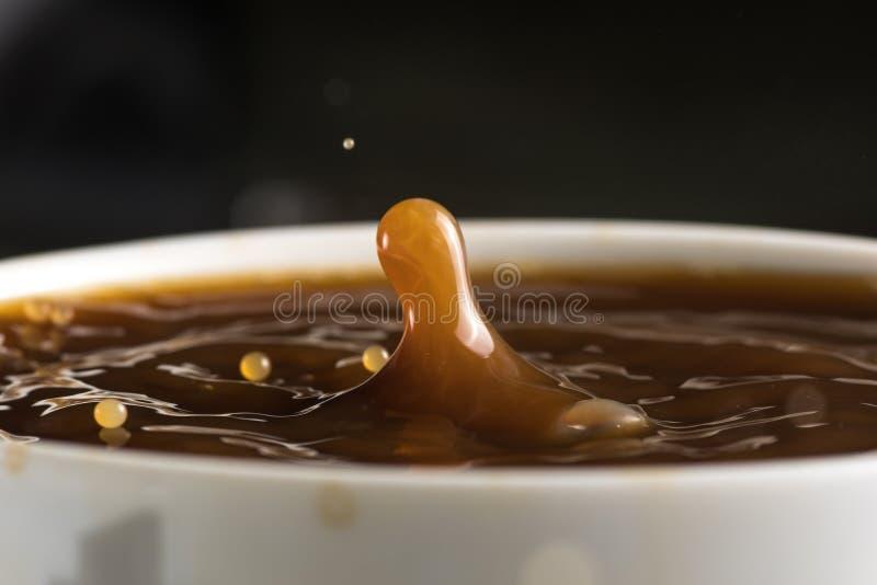 Härliga bristningar av mjölkar droppar på yttersidan av kaffecloseupen arkivfoton