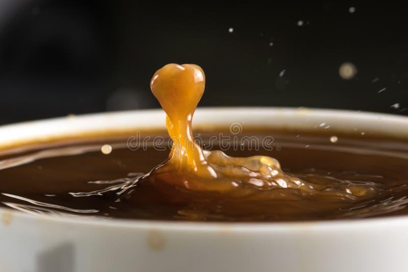 Härliga bristningar av mjölkar droppar på yttersidan av kaffecloseupen royaltyfria foton