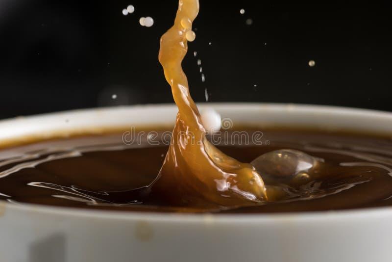 Härliga bristningar av mjölkar droppar på yttersidan av kaffecloseupen arkivbild