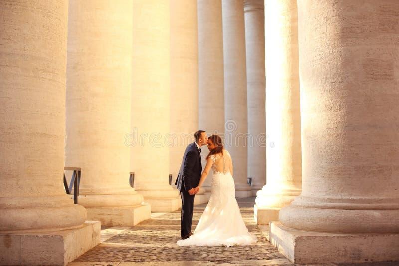 Härliga brud- parinnehavhänder och kyssa nära kolonner arkivfoton