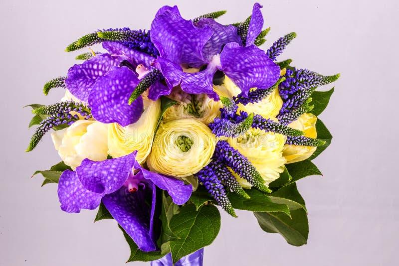 Härliga bukettblommor av den vita ranunculusen, purpurfärgad iris för iris, lupine royaltyfria foton