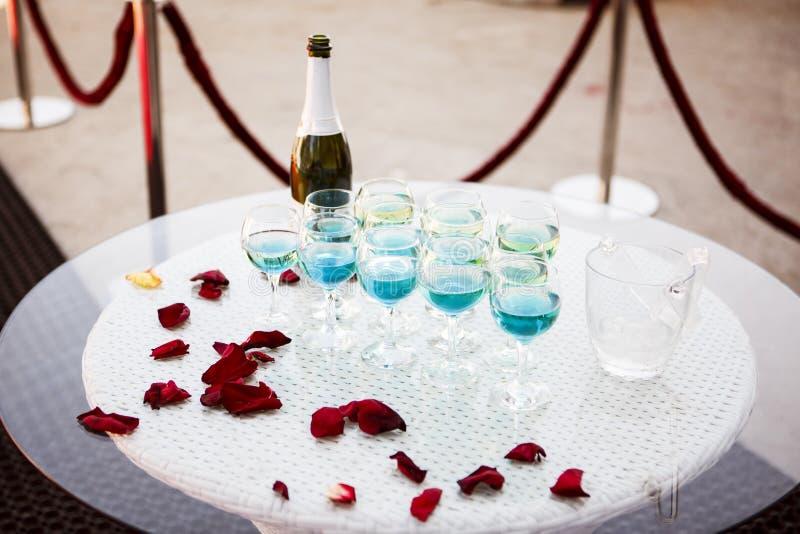 Härliga champagneexponeringsglas på en glass tabell och kronblad av rött r fotografering för bildbyråer
