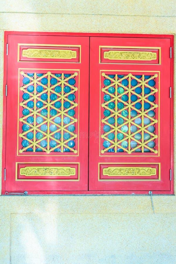 Härliga dörrar och fönster för kinesisk stil träröda med draken royaltyfri bild