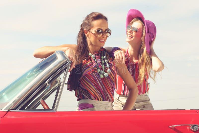 Härliga damer med solexponeringsglas som poserar i en tappningbil i en solig dag, fjädrar sommar royaltyfria bilder