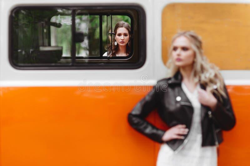 Härliga damer som står nära den retro bilen arkivfoto