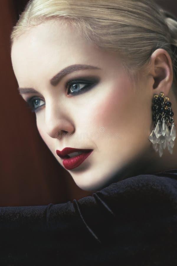 Härliga eleganta blonda kvinnor med röda sammetkanter och smokeyögon royaltyfri fotografi