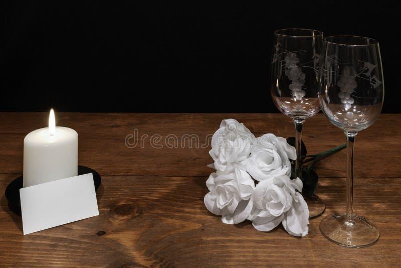 Härliga etsade vinexponeringsglas med den vita vit stearinljus- och namnetiketten för rosor och på trätabellen och mörk bakgrund royaltyfria foton