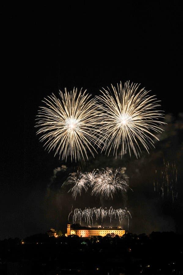 Härliga färgrika fyrverkerier över den Spielberk slotten Vita fyrverkerier på natthimmel Internationell fyrverkerikonkurrensIgnis royaltyfri bild