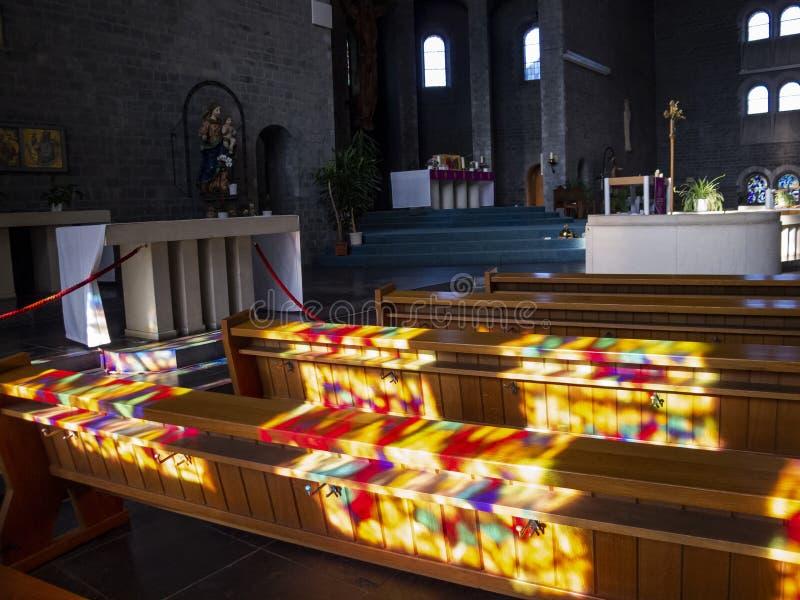 Härliga färgrika solljusfönsterreflexioner på kyrkbänkarna av kyrkan av St Vitus i St Vith, Belgien arkivbild