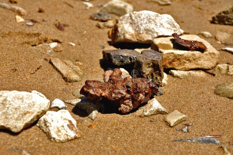 Härliga färgrika stenar på sanden royaltyfri foto