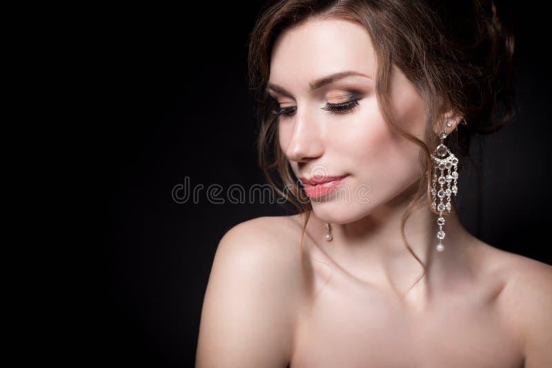 Härliga försiktiga flickastående av bruden i en vit bröllopsklänning med aftonfrisyren med en kant av blommor i hennes hår och royaltyfria foton