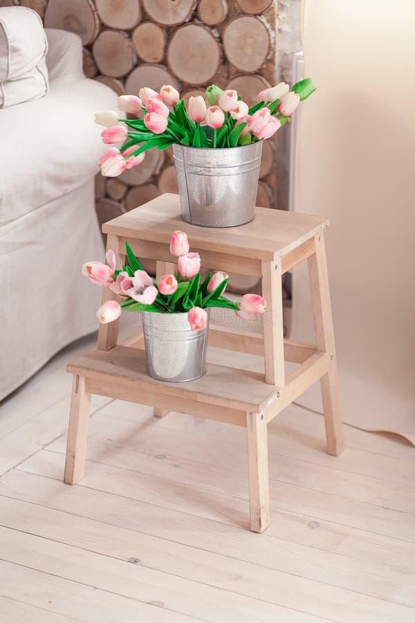 Härliga försiktiga tulpan i en hink på en träställning för blommor nära soffan arkivfoton