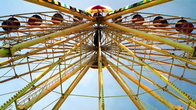 Härliga Ferris Wheel dekorerar med färgrikt, och härlig belysning roterar och visat i den rörliga festivalkarnevalfunfaien arkivfoton