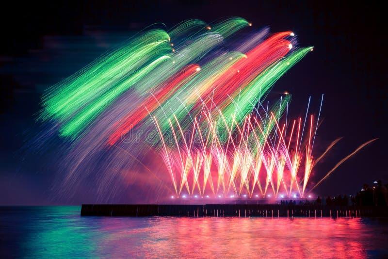 Härliga, festliga färgrika fyrverkerier över vattnet med reflexion arkivfoto