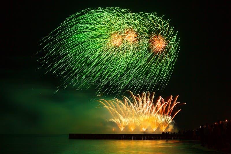 Härliga festliga fyrverkerier gör grön och guld- färg över vattnet med reflexion royaltyfri fotografi