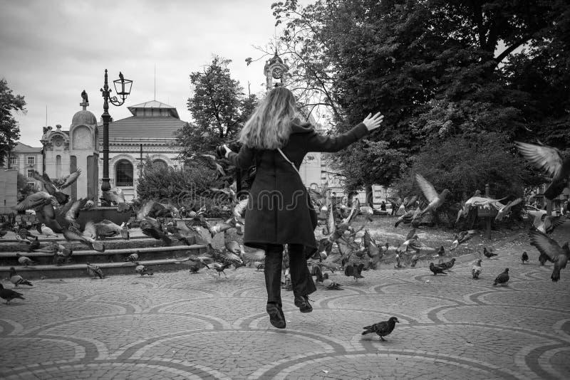 Härliga flickalekar för höst med duvor i Sofia royaltyfri bild