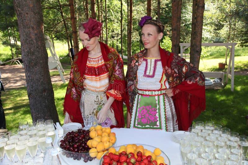 Härliga flickor för mötegäst i nationella ryssdräkter, kappasundresses med vibrerande broderi - folk grupperar hjulet royaltyfri fotografi