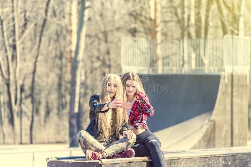 Härliga flickor i tillfällig kläder som gör selfie på skridskon, parkerar arkivbilder