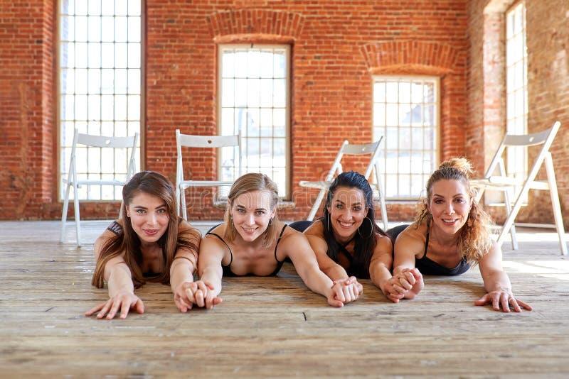Härliga flickor ligger på golvet och ser kameran Begreppet är kvinnligt kamratskap, skönhet och framgång arkivbilder