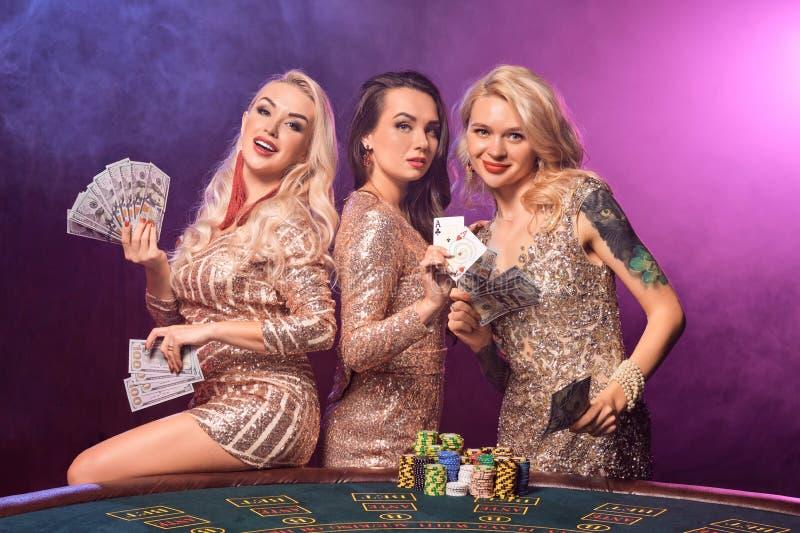 Härliga flickor med perfekta frisyrer och det ljusa sminket poserar anseende på en spela tabell Kasino poker arkivbild