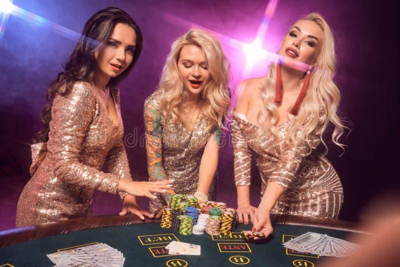 Härliga flickor med perfekta frisyrer och det ljusa sminket poserar anseende på en spela tabell Kasino poker fotografering för bildbyråer