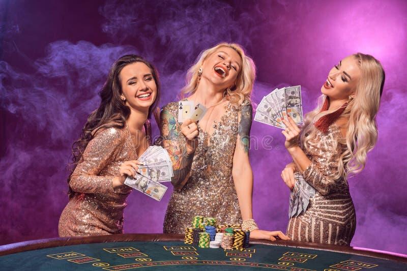 Härliga flickor med perfekta frisyrer och det ljusa sminket poserar anseende på en spela tabell Kasino poker royaltyfri bild