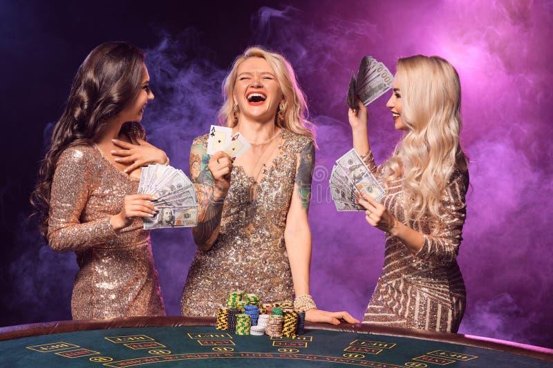 Härliga flickor med perfekta frisyrer och det ljusa sminket poserar anseende på en spela tabell Kasino poker royaltyfria foton