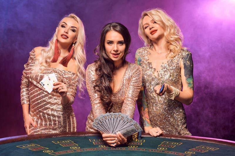 Härliga flickor med perfekta frisyrer och det ljusa sminket poserar anseende på en spela tabell Kasino poker royaltyfri foto