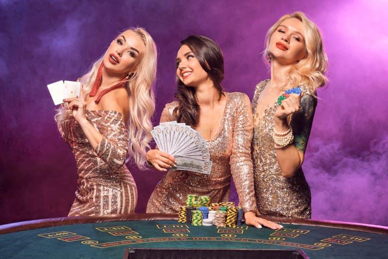 Härliga flickor med perfekta frisyrer och det ljusa sminket poserar anseende på en spela tabell Kasino poker royaltyfria bilder