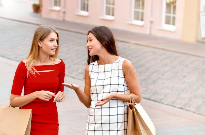 Härliga flickor med shoppingpåsar går vid staden royaltyfria bilder