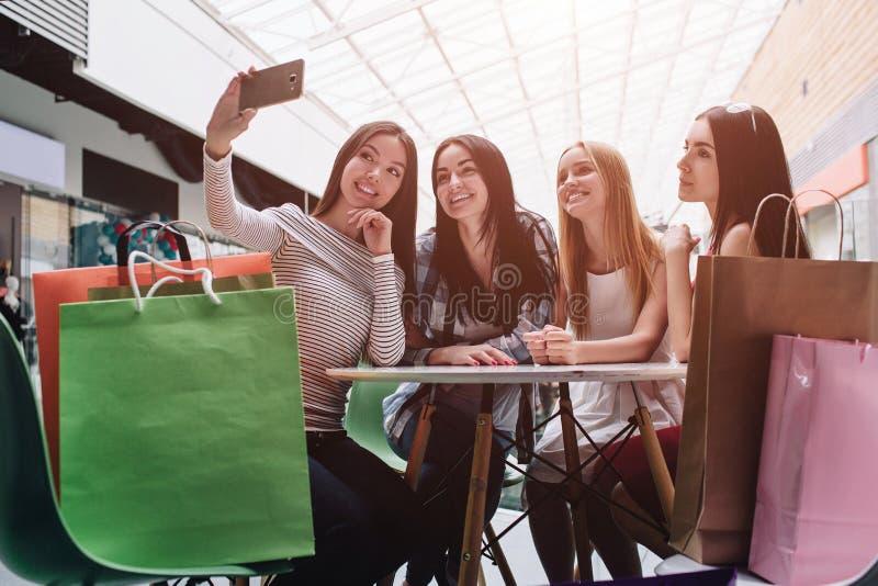 Härliga flickor sitter på tabellen och talande selfie Den asiatiska flickan är den hållande kameran och tabilden av den där arkivfoton
