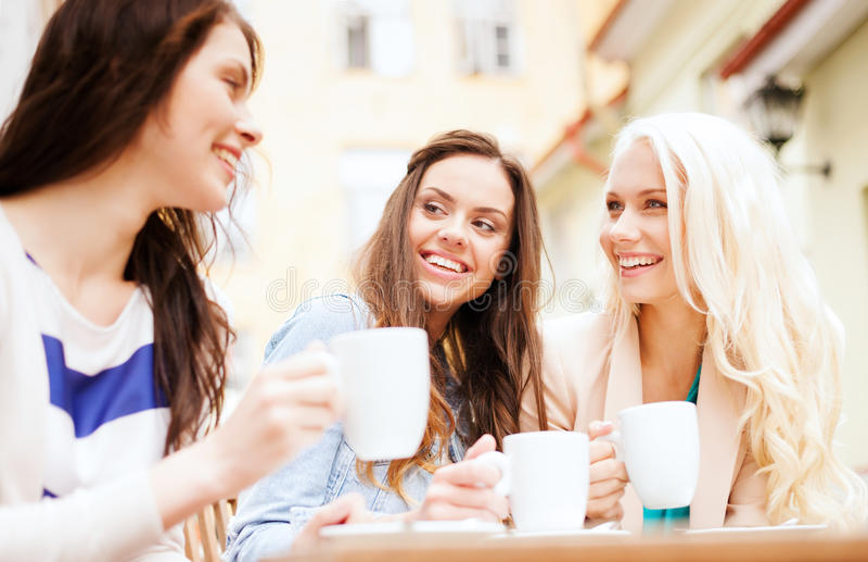 Härliga flickor som dricker kaffe i kafé arkivfoton