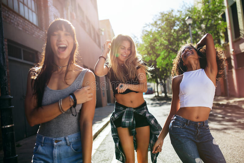 Härliga flickor som går runt om staden och har gyckel royaltyfri fotografi
