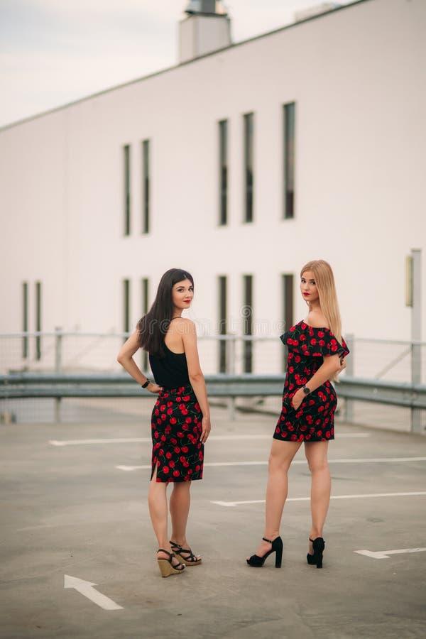 Härliga flickor som poserar för fotografen Två systrar i svart och röd klänning Leende solig dag, sommar fotografering för bildbyråer